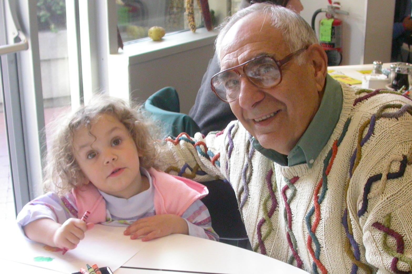 Grandfather and young girl share a moment coloring at a kitchen table, in front of sunny window